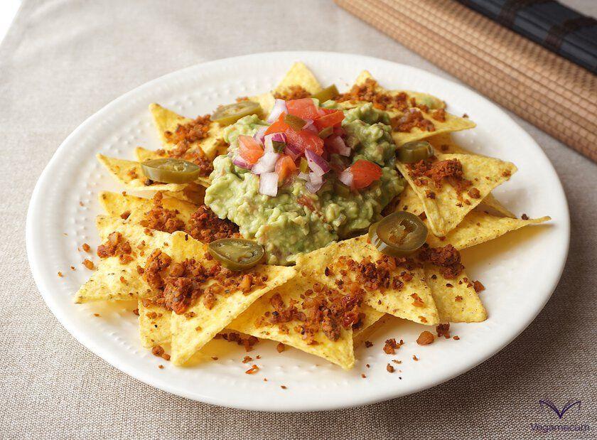 Carne de nuez sabor chorizo sobre nachos con guacamole y pico de gallo